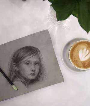 Photo of charcoal drawing and latte at coffee shop