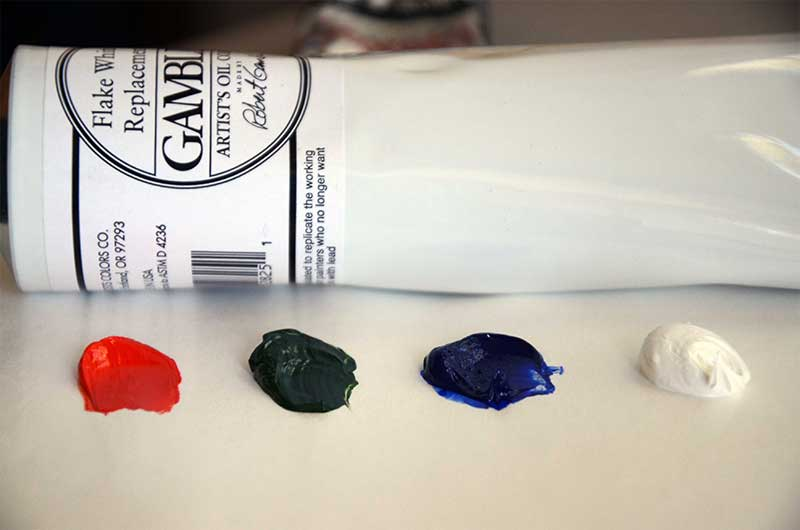 photo of tube of oil paint flake white replacement and oil paint on pallet in cadmium red light, terre verde green and french ultramarine blue